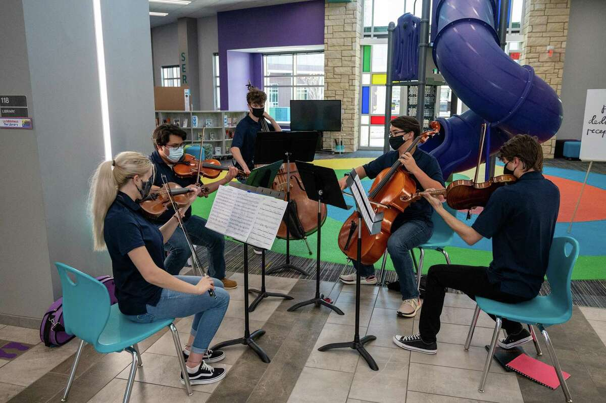 A string quintet plays in the unique library with a reward slide in the middle of it. The new Fox Elementary in Klein ISD was designed with input from students.