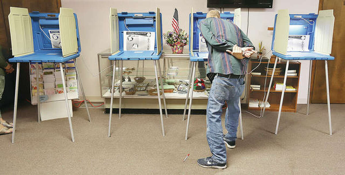 A voter in Alton Precinct 24 bends over Tuesday morning to read the voting instructions before filling out his ballot in the Messiah Lutheran Church, 920 Milton Road.
