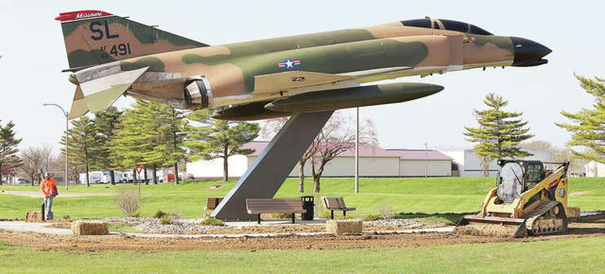 Employees of Stutz Excavating Inc. in Alton were finishing the grading and grass seeding Tuesday around a new sidewalk recently poured at the F4 Phantom fighter jet in front of St. Louis Regional Airport in Bethalto.