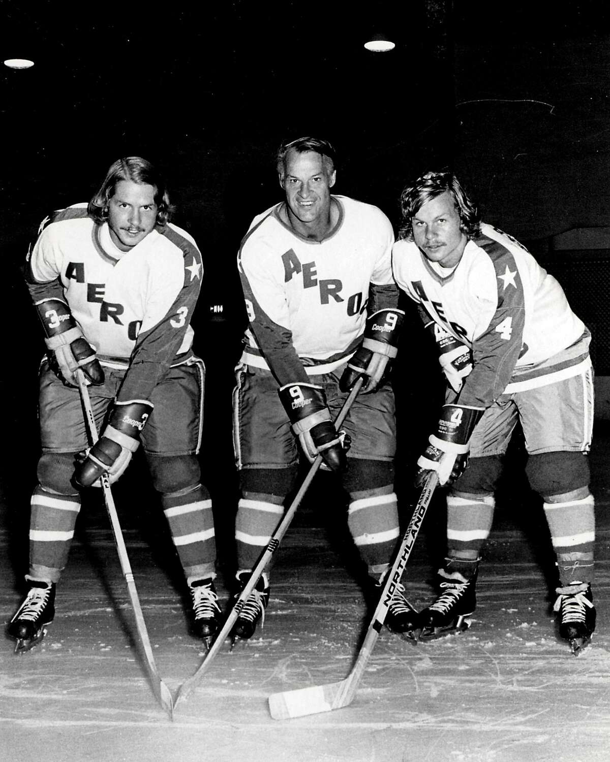 """In an Aug. 3, 1973 file photo, former Detroit Red Wings great Gordie Howe, center, is flanked by sons Marty, left, and Mark as they try their new Houston Aeros uniforms in St. Clair Shores, Mich. A made-for-TV movie, """"Mr. Hockey: The Gordie Howe Story,"""" focuses on the season the Hall of Famer teamed up with his sons in Houston. The U.S. premiere of the film is Saturday, May 4, 2013. (AP Photo/The Macomb Daily, David Posavetz, FILE)"""