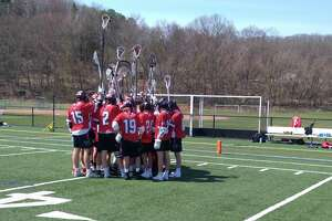 Pomperaug's boys lacrosse team huddles after its 10-9 season-opening loss at New Milford High School in New Milford, Conn., on April 10, 2021. The No. 13 jersey of junior Ryan Rutledge, who died on April 5, hangs behind the team's bench.