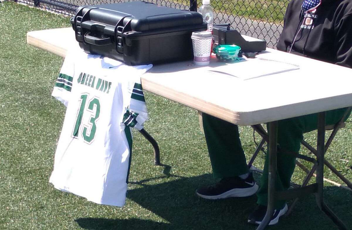 A New Milford No. 13 jersey hangs at the scorer's table after the team's 10-9 win over Pomperaug on April 10, 2021, in New Milford, Conn. The jersey honored Pomperaug junior Ryan Rutledge, who died on April 5.