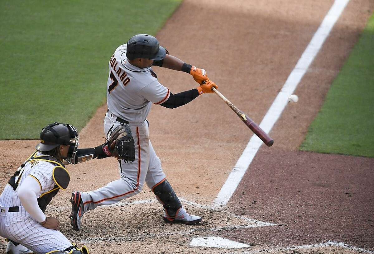 SAN DIEGO, CA - APRIL 7: Donovan Solano #7 of the San Francisco Giants hits a sacrifice fly out during the tenth inning of a baseball game against the San Diego Padres at Petco Park on April 7, 2021 in San Diego, California. (Photo by Denis Poroy/Getty Images)
