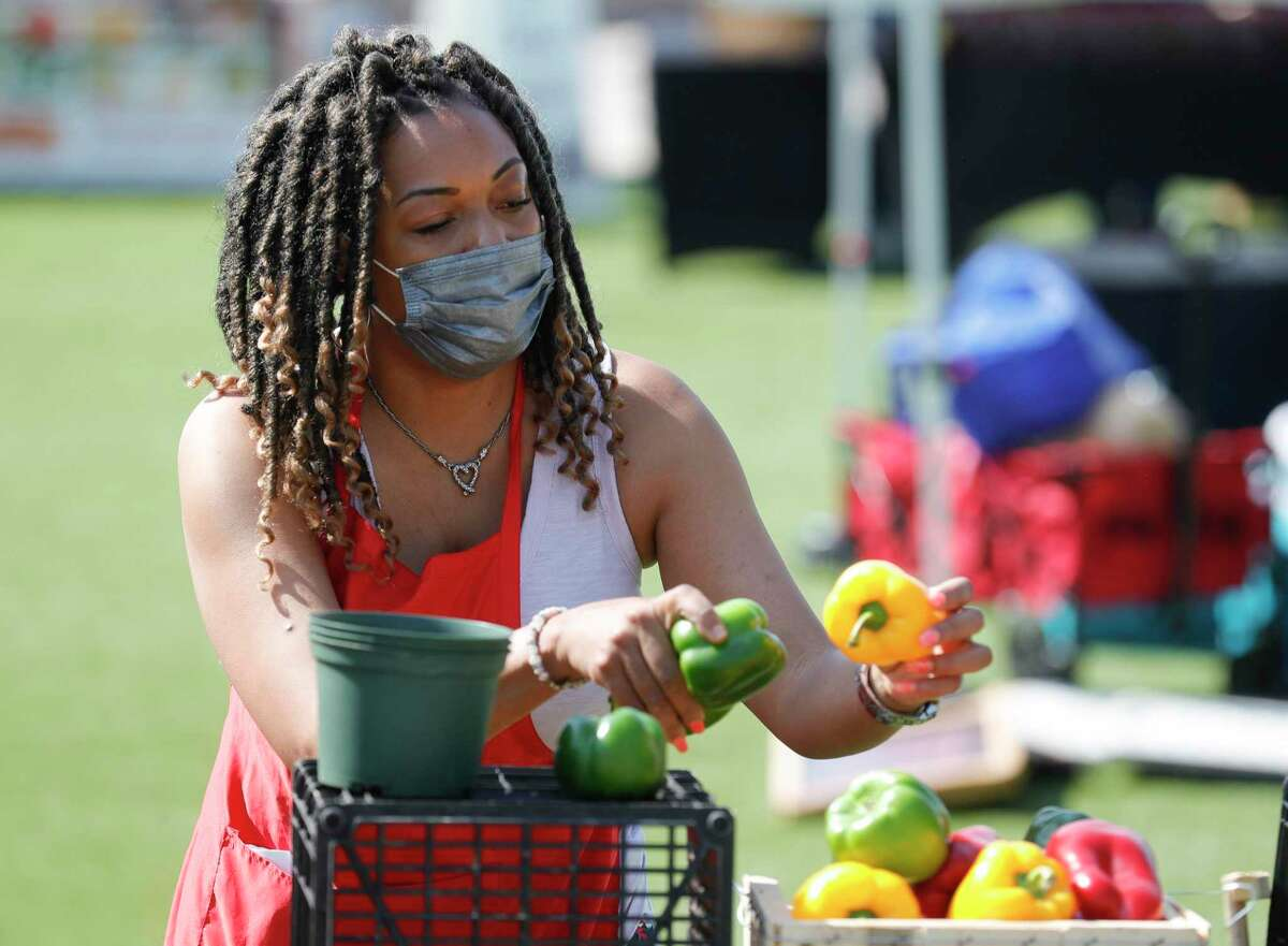 Cre Johnson sorts through produce during Your Neighborhood Farmer's Market, Saturday, April 10, 2021, in Shenandoah.