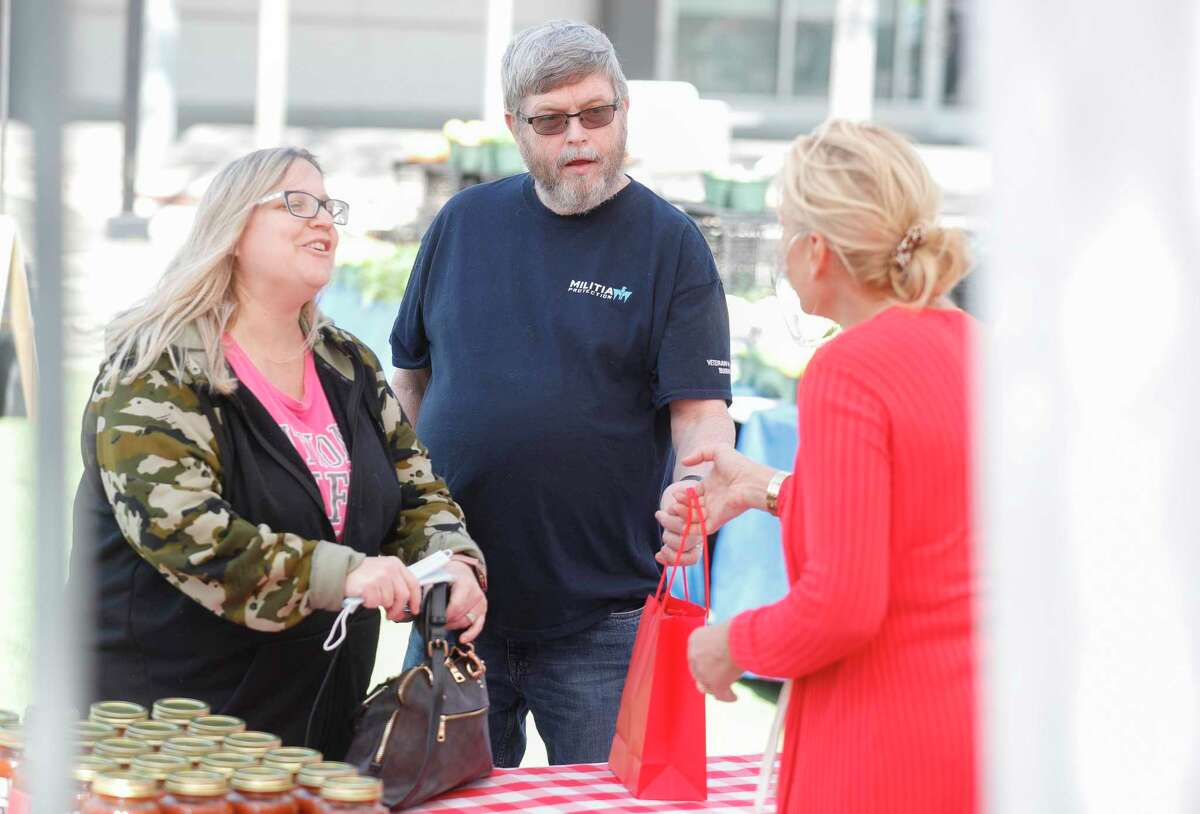 Charles Oquin and his wife, Khrista, shop at Mary Anne's Spaghetti during Your Neighborhood Farmer's Market, Saturday, April 10, 2021, in Shenandoah.