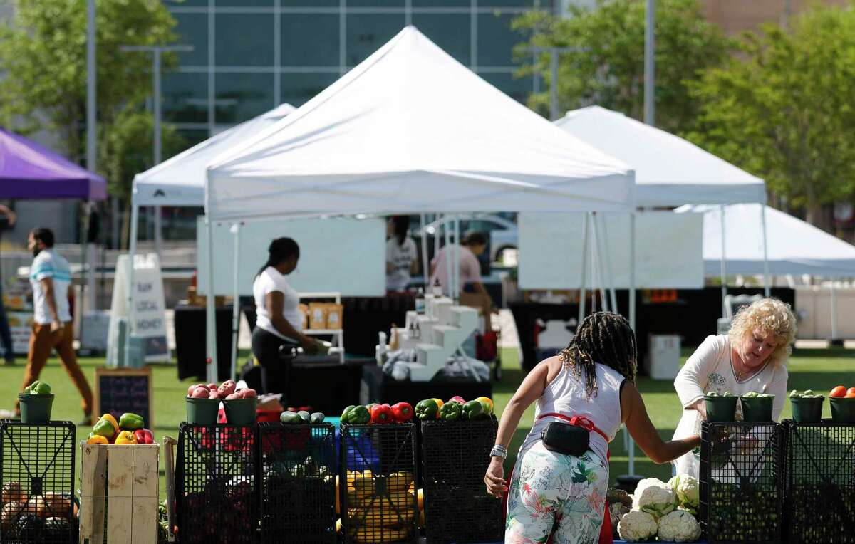 Shoppers go through booths during Your Neighborhood Farmer's Market, Saturday, April 10, 2021, in Shenandoah.