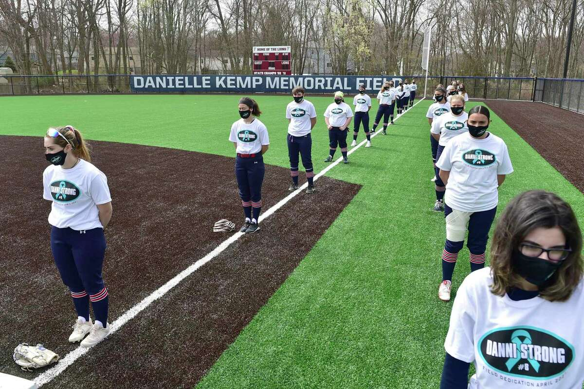 """Milford, Connecticut -Saturday- April 10, 2021: Softball players stand for a moment of silence for Foran H.S. softball player Danielle """"Danni"""" Kemp, who lost her battle with cancer at 19, during the dedication of the Foran High School Danielle Kemp Memorial Field on the opening day of high school spring sports Saturday before the Jonathon Law H.S. vs. Foran H.S. softball game."""