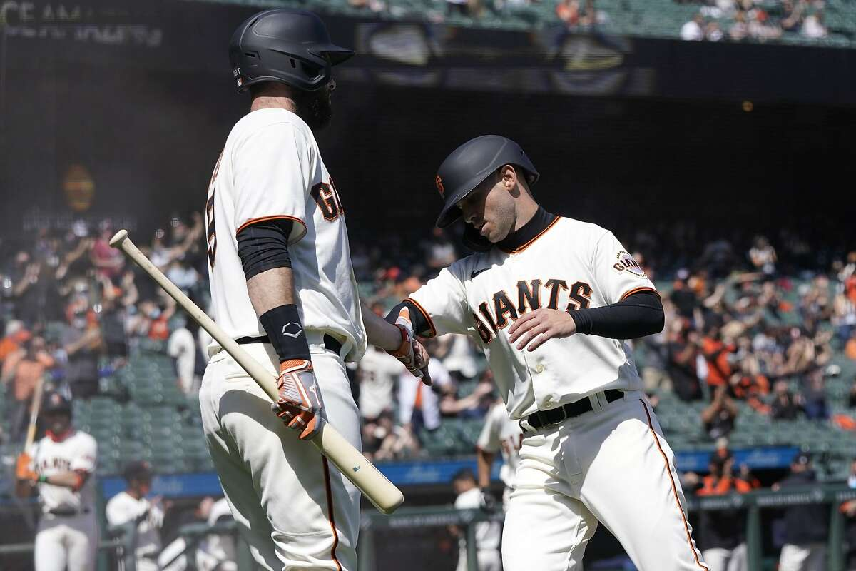 San Francisco Giants' Tommy La Stella, right, is congratulated by Brandon Belt after scoring against the Colorado Rockies during the third inning of a baseball game in San Francisco, Saturday, April 10, 2021. (AP Photo/Jeff Chiu)
