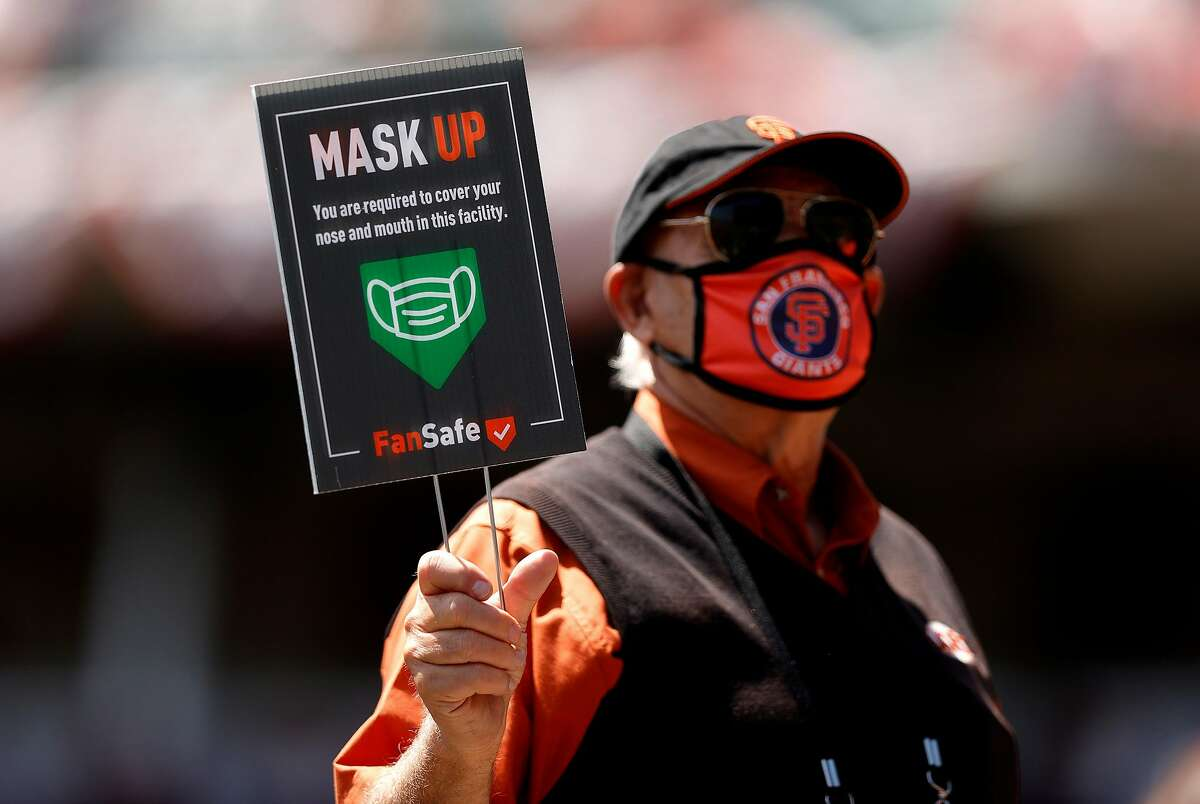 An usher holds up a sign reminding fans to wear a mask during a San Francisco Giants game at Oracle Park in San Francisco, California. As more people get vaccinated and coronavirus infections slow, wearing masks outdoors has become a topic of debate.