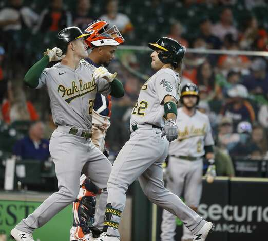 Oakland Athletics Ramon Laureano (22) and Mark Canha (20) celebrate Laureano's two-run home run off of Houston Astros starting pitcher Jose Urquidy during the fifth inning of an MLB baseball game at Minute Maid Park, in Houston, Saturday, April 10, 2021. Photo: Karen Warren/Staff Photographer / @2021 Houston Chronicle