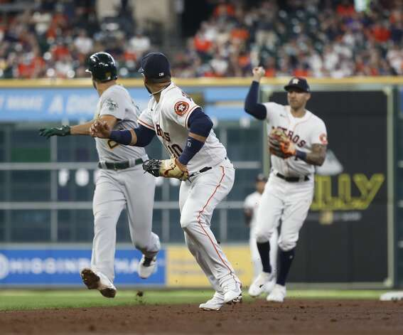 Oakland Athletics first baseman Matt Olson (28) gets caught in a rundown with Houston Astros shortstop Carlos Correa (1) and first baseman Yuli Gurriel (10) after his RBI single during the fourth inning of an MLB baseball game at Minute Maid Park, in Houston, Saturday, April 10, 2021. Photo: Karen Warren/Staff Photographer / @2021 Houston Chronicle