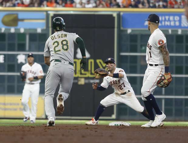 Oakland Athletics first baseman Matt Olson (28) gets caught in a rundown with Houston Astros shortstop Carlos Correa (1) and second baseman Jose Altuve (27) after his RBI single during the fourth inning of an MLB baseball game at Minute Maid Park, in Houston, Saturday, April 10, 2021. Photo: Karen Warren/Staff Photographer / @2021 Houston Chronicle