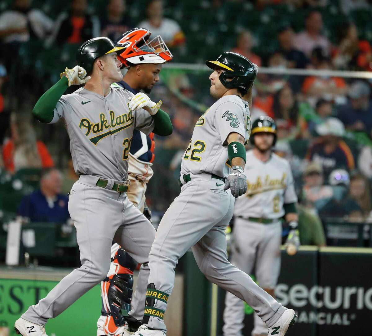 Oakland Athletics Ramon Laureano (22) and Mark Canha (20) celebrate Laureano's two-run home run off of Houston Astros starting pitcher Jose Urquidy during the fifth inning of an MLB baseball game at Minute Maid Park, in Houston, Saturday, April 10, 2021.