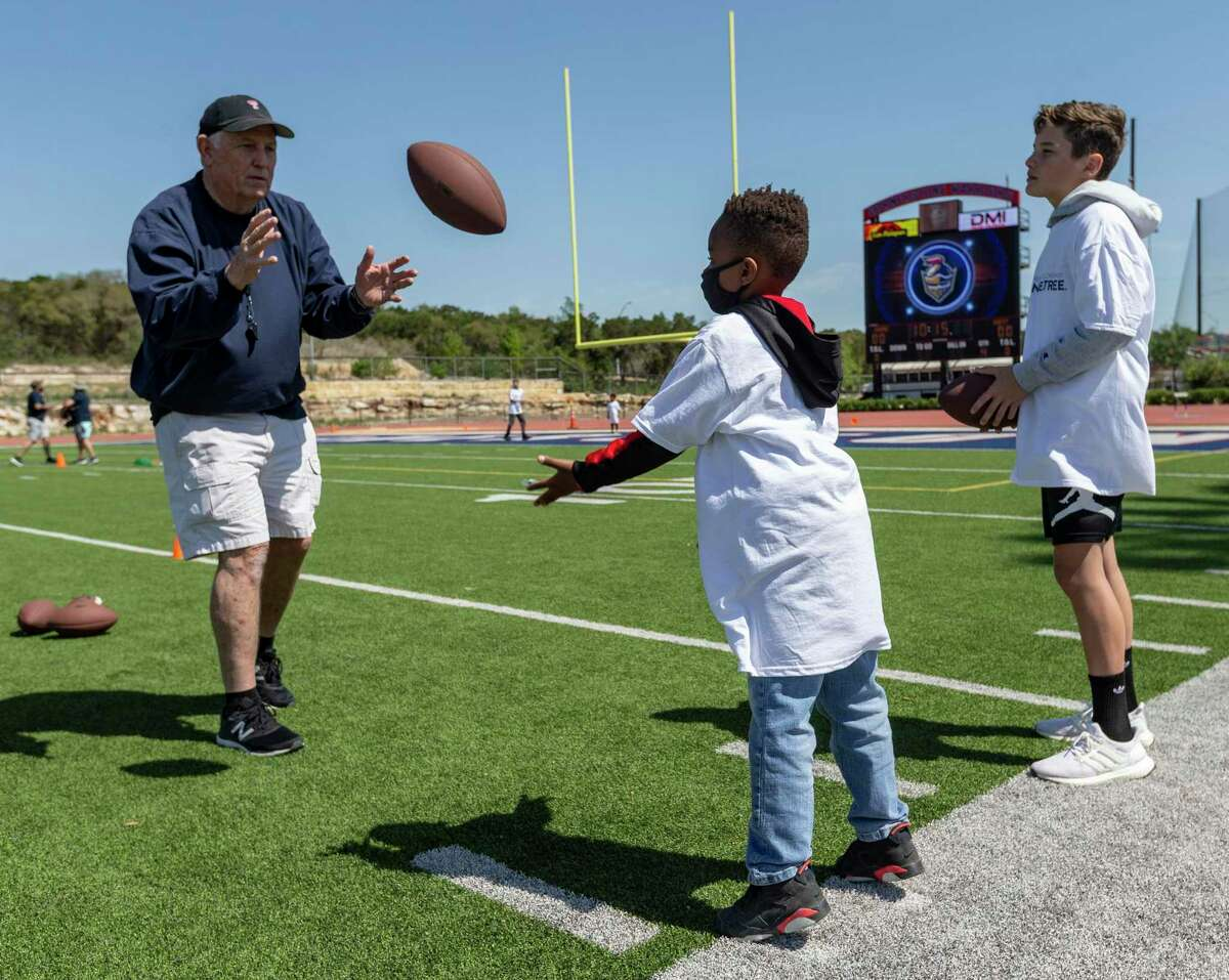 Zayden, center, learns how to properly throw a football Saturday, April 10, 202, at the hands of former Texas Tech quarterback Joe Matulich, left, as Tucker Stricklin waits his turn during a sports cap at Cornerstone Christian Schools field.