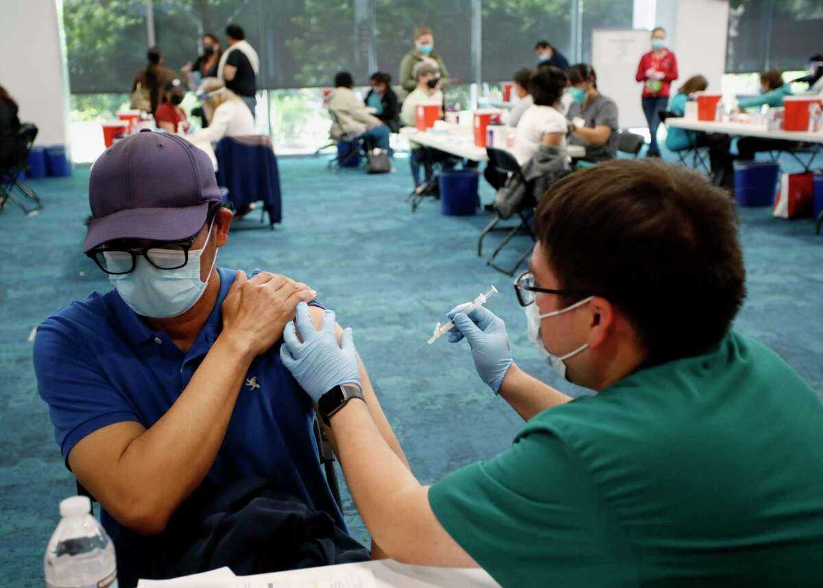 Mariano Zelaya (left) of Redwood City receives his vaccination from Carlos Martinez at the Facebook headquarters vaccine distribution center in Menlo Park. Companies are increasingly requiring job applicants be vaccinated.