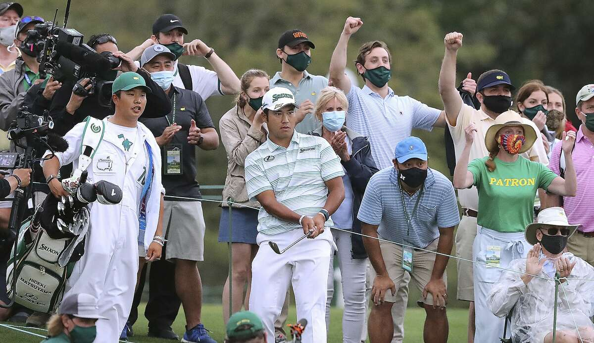 The crowd cheers Hideki Matsuyama as he chips it close to the cup to save par on 18 and finish at 11-under.