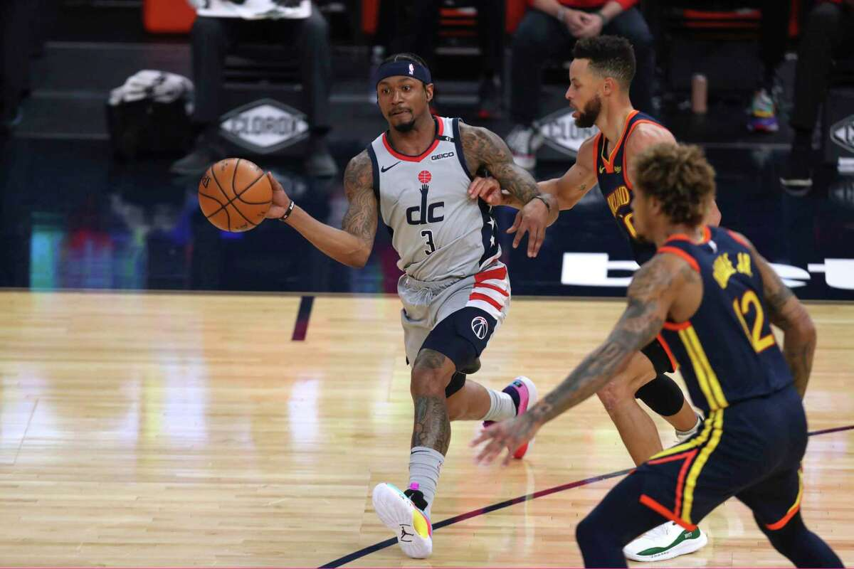 Washington Wizards forward Bradley Beal, left, passes the ball as Golden State Warriors forward Kelly Oubre Jr., front, and guard Stephen Curry, rear, defend during the first half of an NBA basketball game in San Francisco, Friday, April 9, 2021. (AP Photo/Jed Jacobsohn)
