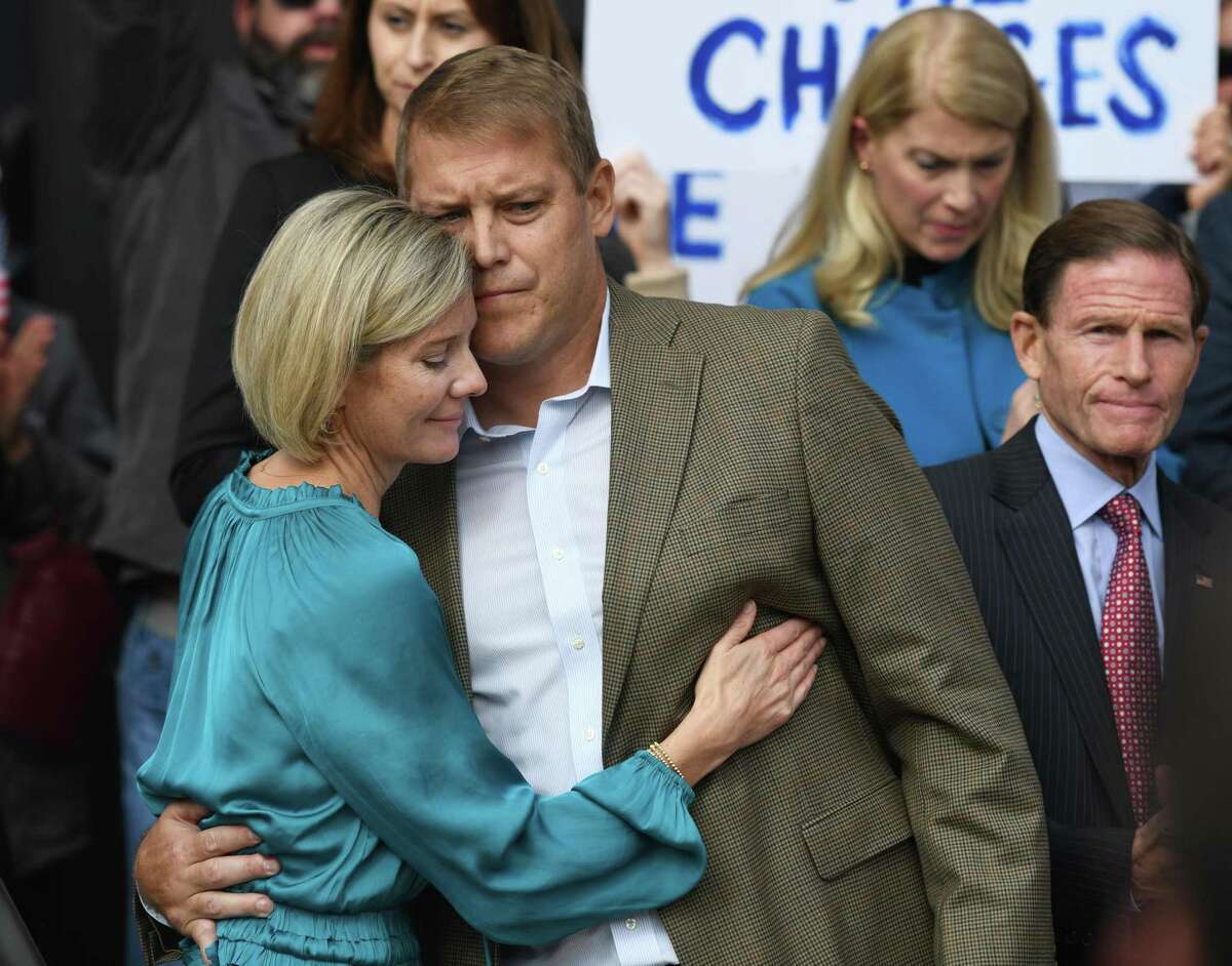 Darien man Scott Hapgood hugs his wife, Kallie Hapgood, at Town Hall in Darien, Conn. Monday, Oct. 28, 2019 as U.S. Sen. Richard Blumenthal, D-Conn., and the town show support for him in his manslaughter charge from a family vacation in Anguilla.