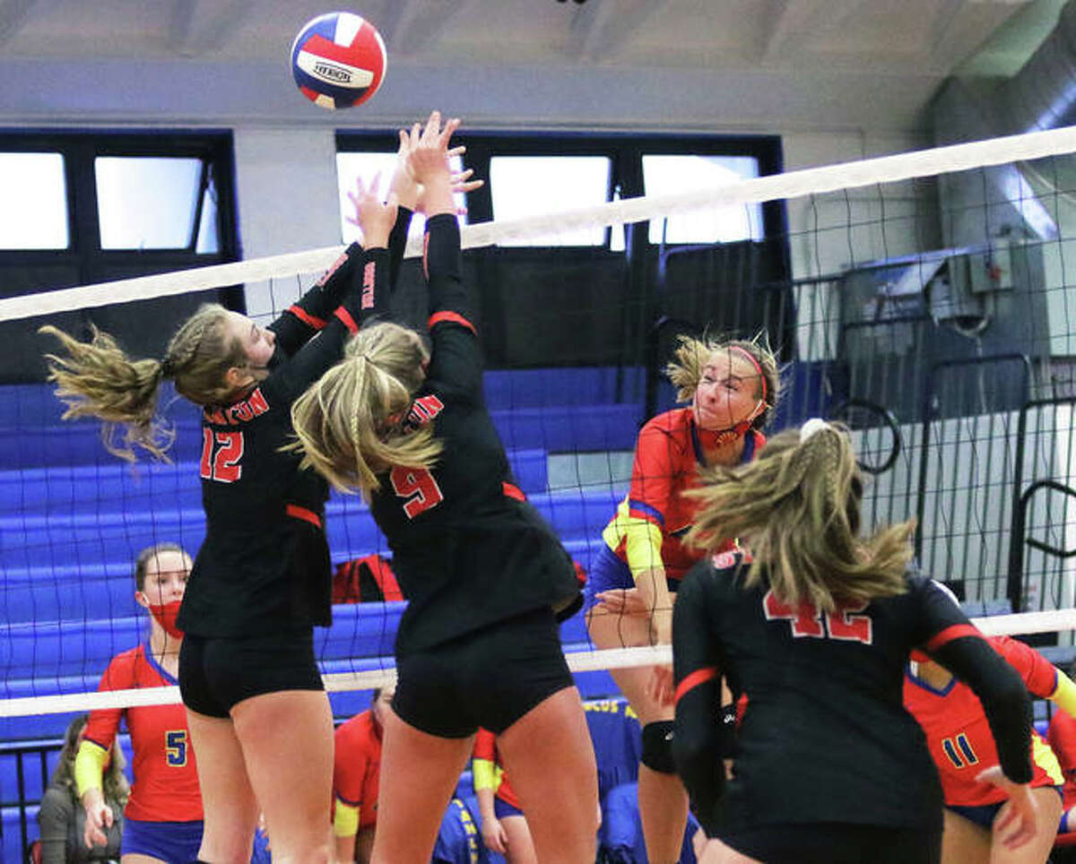 Roxana's Macie Lucas (middle) hits over the block by Staunton's Haris Legendre (12) and Danielle Russell (9) in a March 22 match in Roxana. On Saturday, Lucas and the Shells were in Wood River and beat their rival Oilers in two sets.