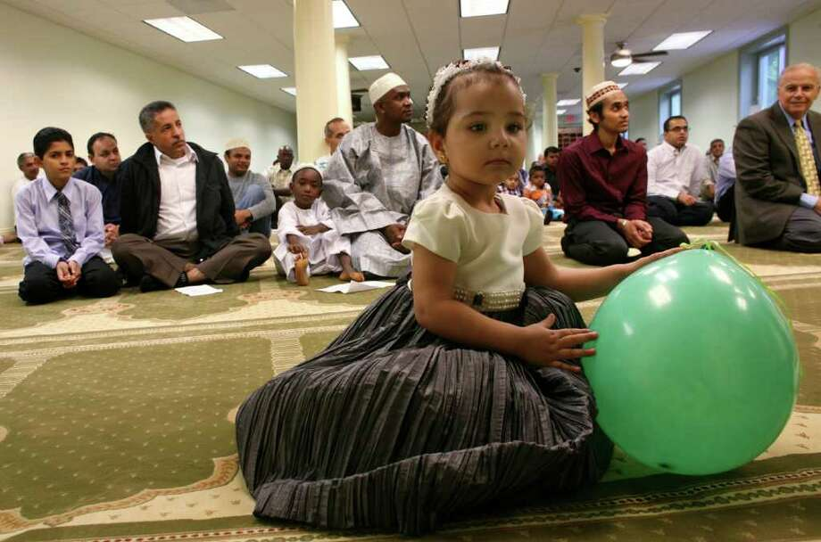Two year old Mena Kattaria plays with a balloon before the start of prayers at the ICCNY Islamic Center which was celebrating the last day of Ramadan Friday morning. Photo: David Ames / Stamford Advocate Freelance