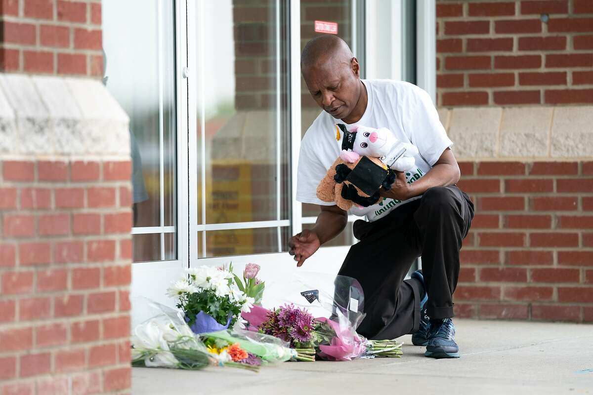 Jack Logan, founder of Put Down the Guns Young People, places stuffed animals and flowers outside of Riverview Family Medicine and Urgent Care after the fatal shooting of Dr. Robert Lesslie and five others in Rock Hill, S.C. Authorities said former NFL player Phillip Adams shot them before fatally shooting himself.