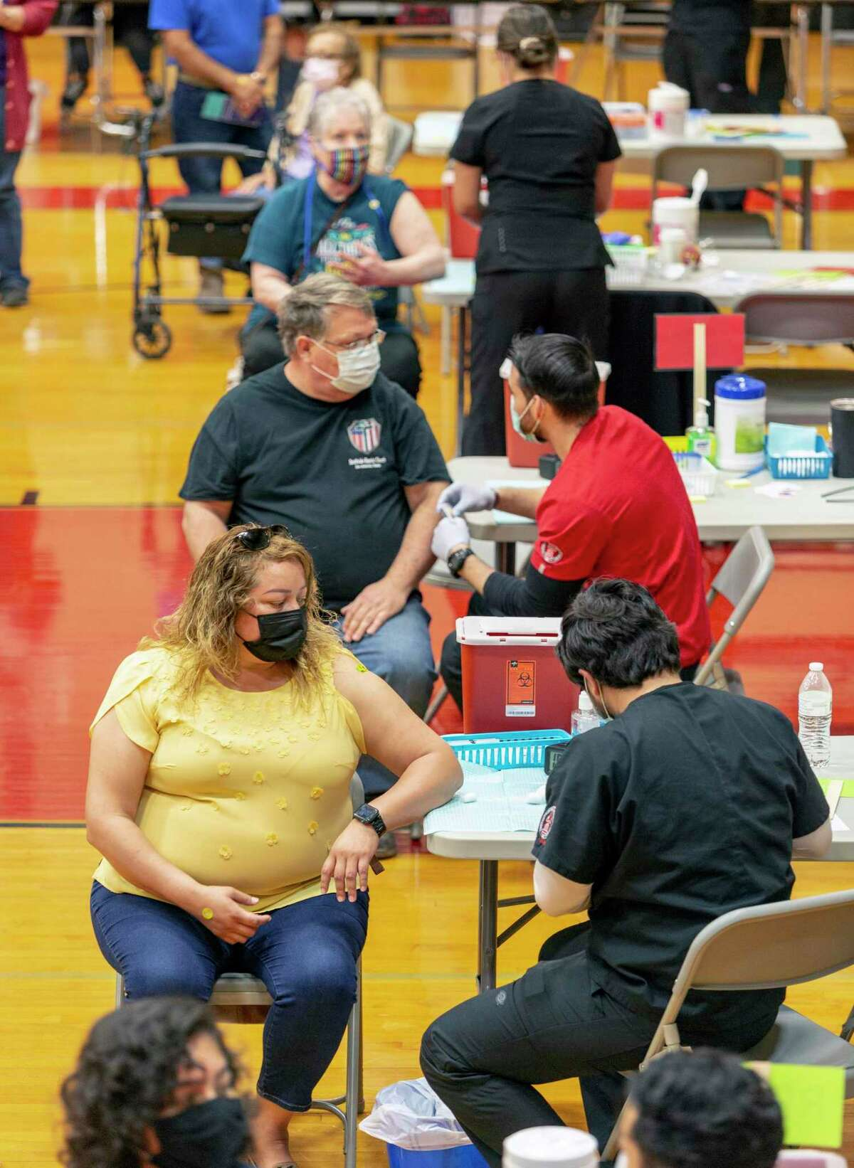 """Alma Diaz, front left, prepares to receive her COVID-19 coronavirus vaccine Saturday, April 10, 2021 at Southside High School during a joint vaccination clinic held by UIW and Southside ISD. """"I'm glad I got this one,"""" Diaz said, referring to the Johnson & Johnson vaccine, which requires just one shot."""