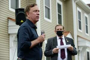 CT Governor Ned Lamont speaks at a Greenwich Communities plaque dedication at its Armstrong Court affordable housing apartment complex in April with Greenwich Communities board Chair Sam Romeo to his right. The proposal to create a new affordable housing trust fund could be a boon to more projects like Armstrong Court by providing private money for development projects.