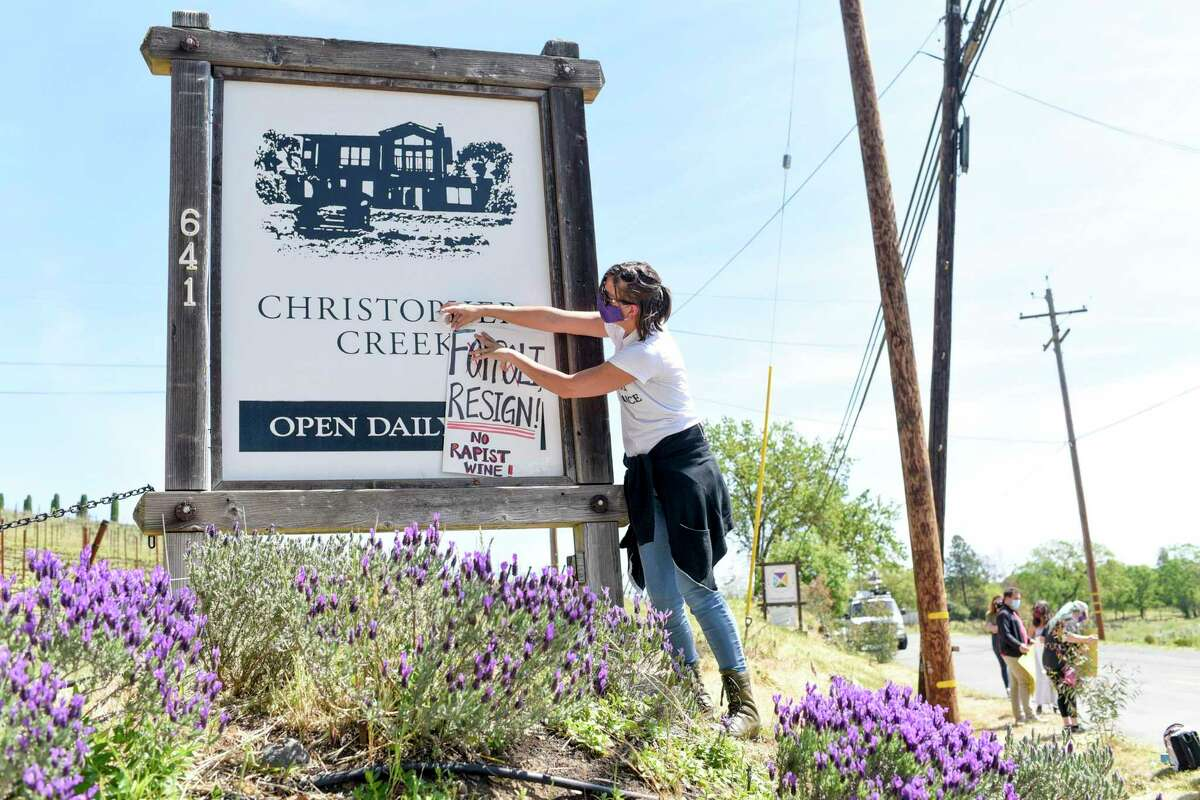 Hollie Clausen of Santa Rosa puts a sign calling for Windsor Mayor Dominic Foppoli to resign on the sign for Christopher Creek Winery at a rally in Healdsburg.