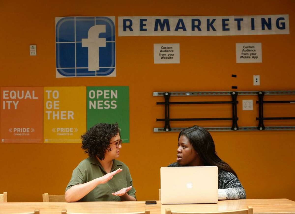 Holly Hagen (left), product designer with Ads Growth, talks with Facebook product design intern Zainab Aliyu at Facebook in Menlo Park.