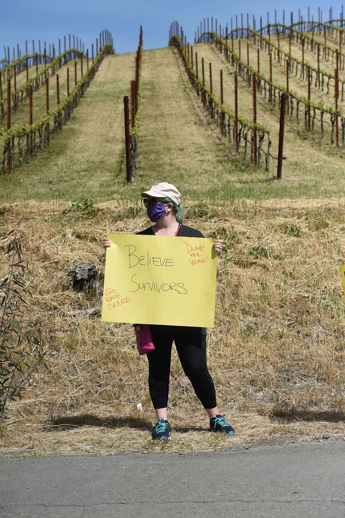 """Allegra Wilson of Santa Rosa holds a sign reading """"believe survivors"""" at a rally calling for Windsor Mayor Dominic Foppoli to resign outside Christopher Creek Winery in Healdsburg."""