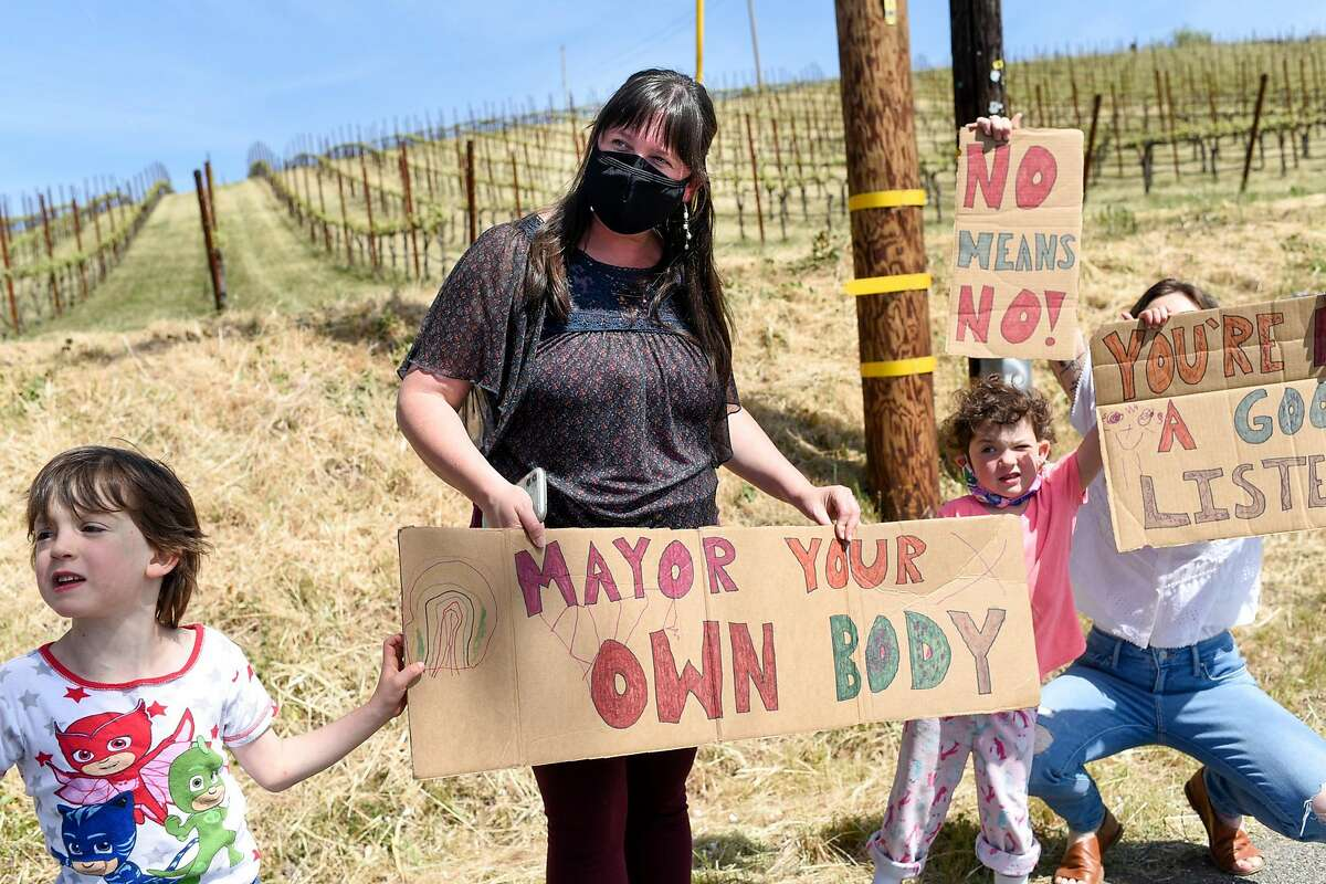 Sophia Williams (center) one of the women who came forward with allegations of sexual assault against Windsor Mayor Dominic Foppoli, her son, Benji Henderson, 5, daughter, Gracie Henderson, 4, and her business partner, Lea Ritter, hold signs at a rally calling for Windsor Mayor Dominic Foppoli to resign outside Christopher Creek Winery in Healdsburg.