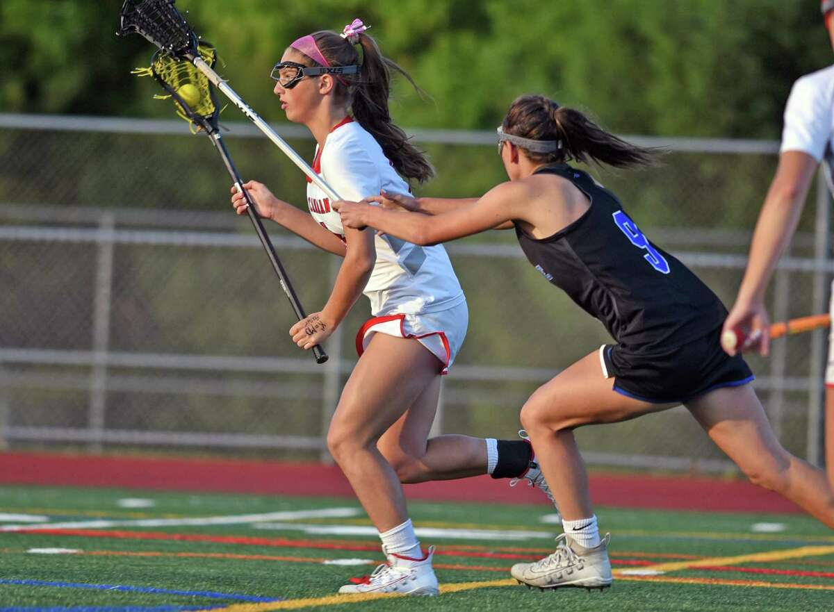 New Canaan's McKenna Hardenl , left, charges the net as Darien's Kate Bellissimo pursues during the FCIAC girls lacrosse championship in 2019 at Testa Field in Norwalk.
