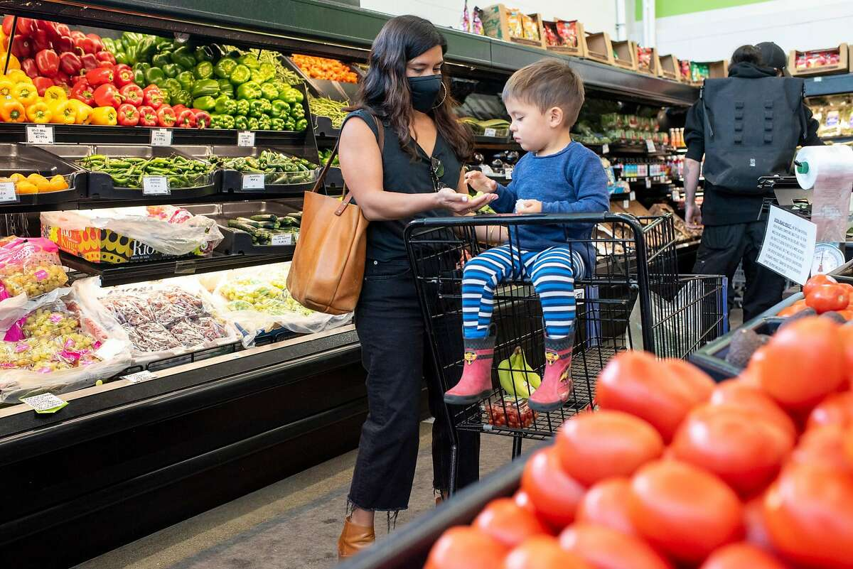 Lauren Seto of Oakland shops with her son, Luca, 2, at the Community Foods Market in Oakland. The grocery store is struggling because of plunging sales during the second half of the pandemic.