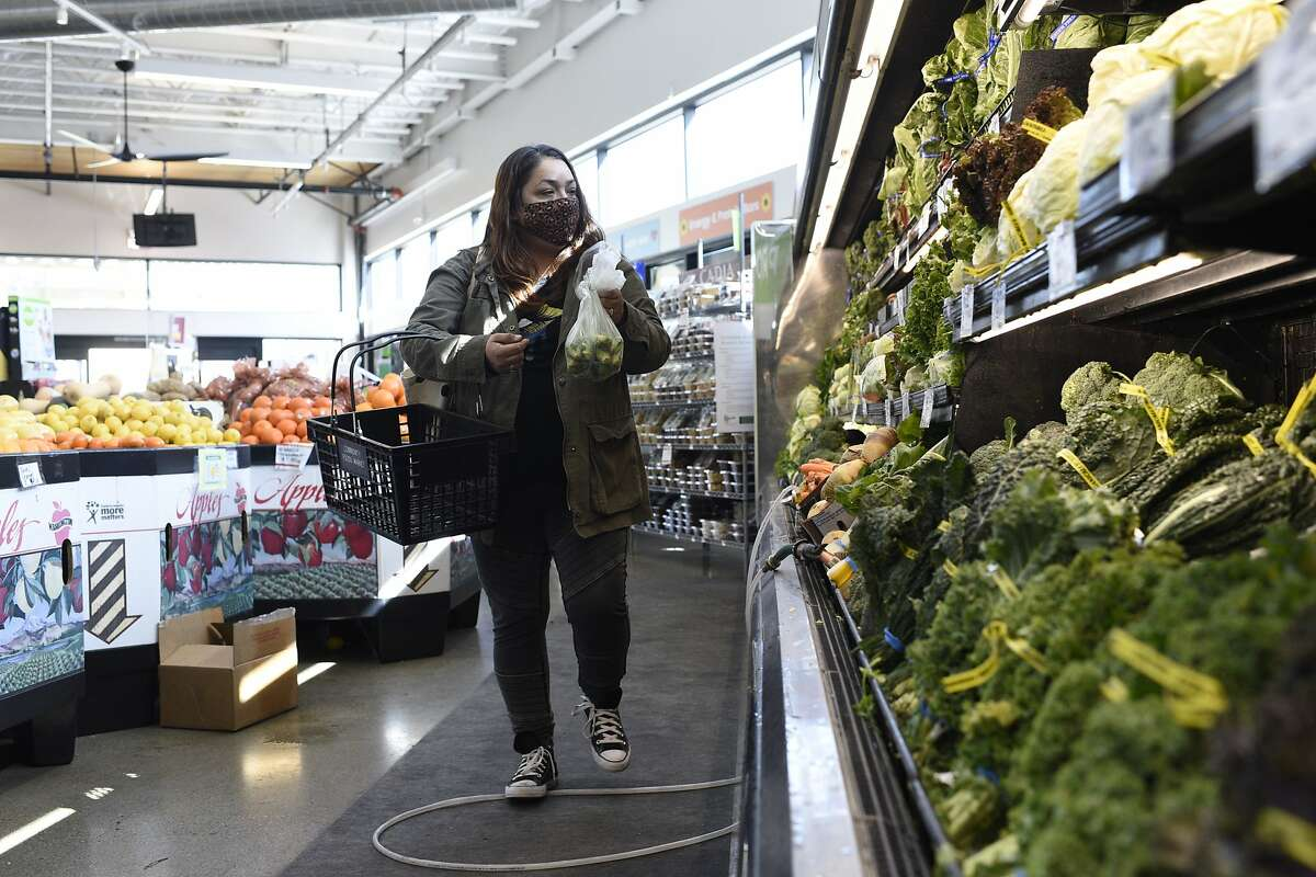 Anissa Cisneros shops at Community Foods Market in West Oakland. Sales have fallen at the store, putting it at risk of closure.