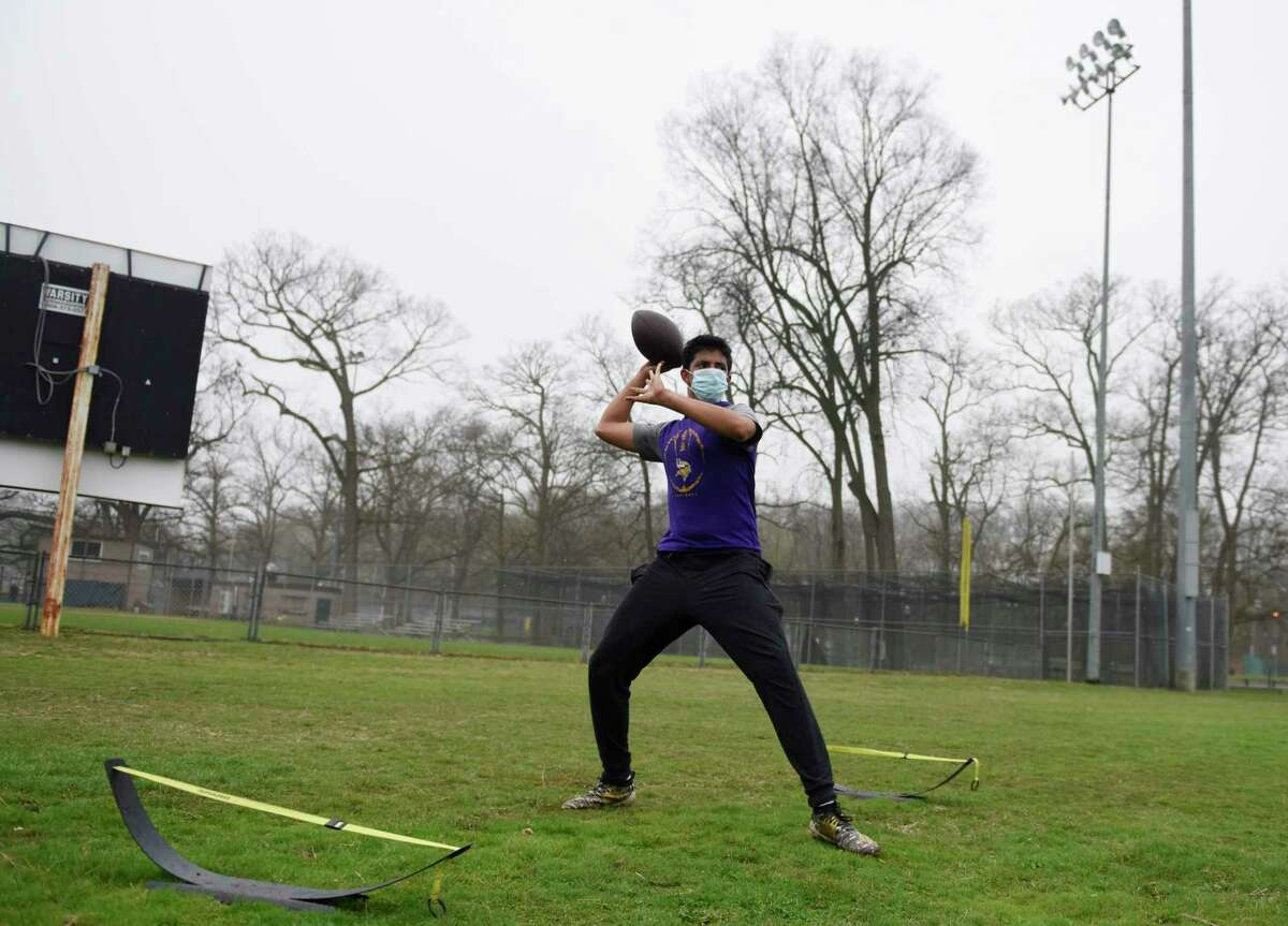 Westhill High School sophomore quarterback Anwar Tahir trains on a rainy day at Scalzi Park in Stamford, Conn. Sunday, April 11, 2021. The area received consistent mist and light rain throughout the day Sunday.