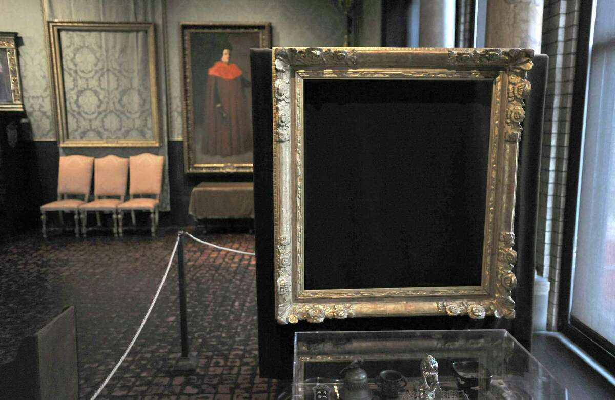 """FILE - In this Thursday, March 11, 2010 file photo, empty frames from which thieves took """"Storm on the Sea of Galilee,"""" left background, by Rembrandt and """"The Concert,"""" right foreground, by Vermeer, remain on display at the Isabella Stewart Gardner Museum in Boston. The paintings are among 13 works stolen by burglars from the museum in the early hours of March 18, 1990. The FBI said Monday, March 18, 2013, it believes it knows the identities of the thieves who stole the art. Richard DesLauriers, the FBI's special agent in charge in Boston, says the thieves belong to a criminal organization based in New England the mid-Atlantic states. (AP Photo/Josh Reynolds, File)"""