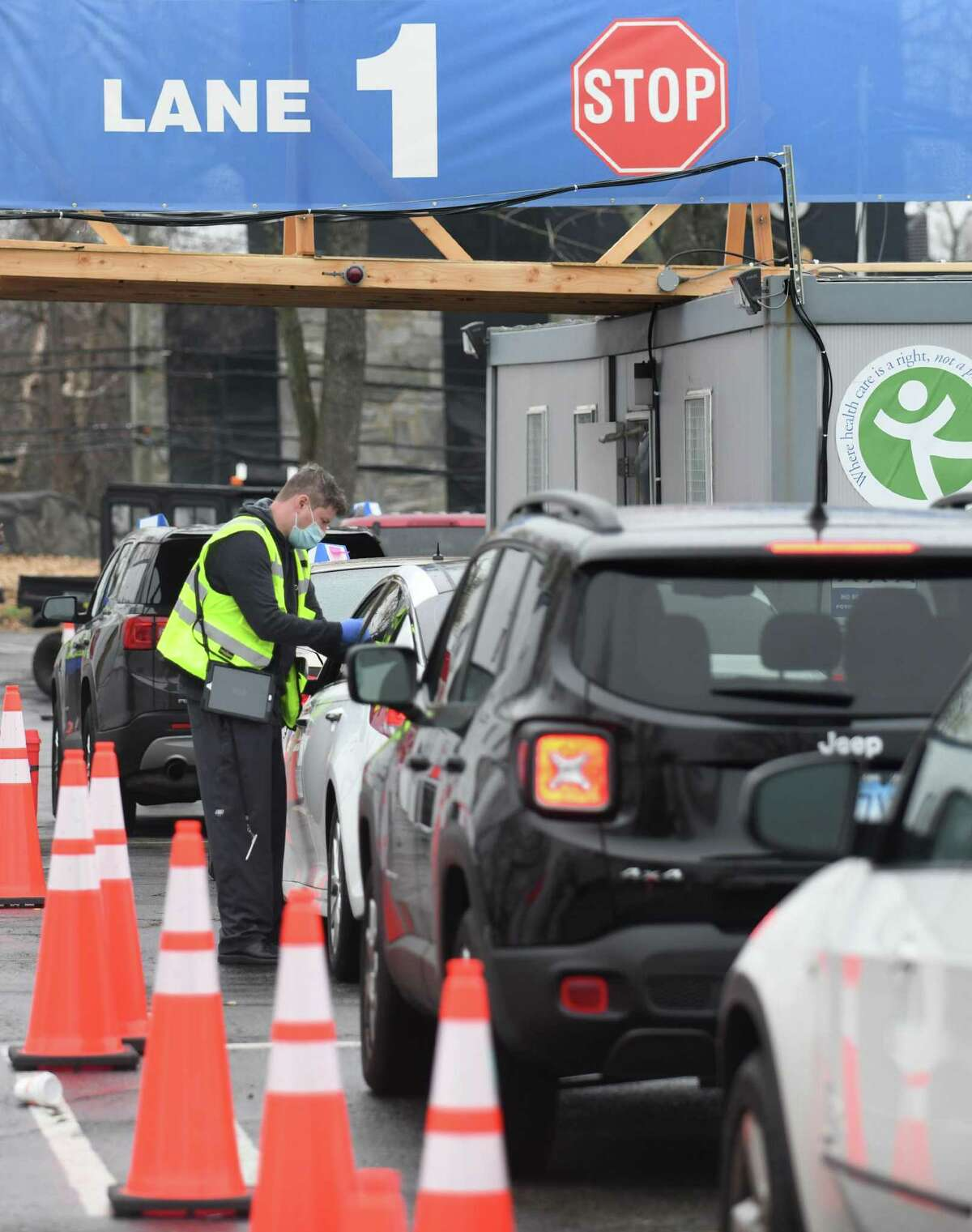 CHC staff checks in patients from their cars waiting to be vaccinated at the Community Health Center Drive-Thru Vaccination Clinic in Stamford, Conn. Sunday, April 11, 2021. Hundreds of Norwalk Public School students 16 and older received the first dose of the COVID-19 vaccine Sunday at the clinic.
