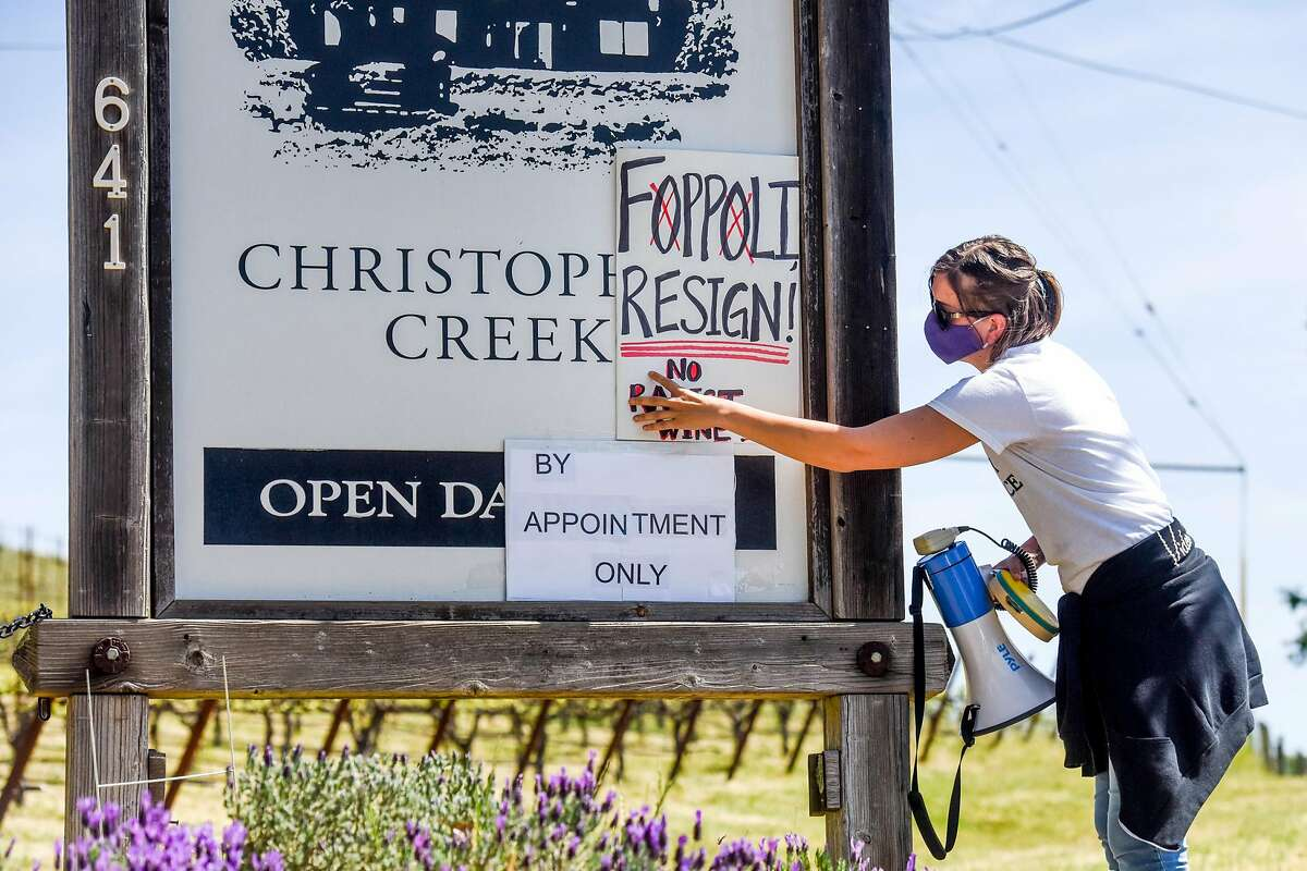 Hollie Clausen of Santa Rosa holds up a sign calling for Windsor Mayor Dominic Foppoli to resign at a rally outside Christopher Creek Winery in Healdsburg.