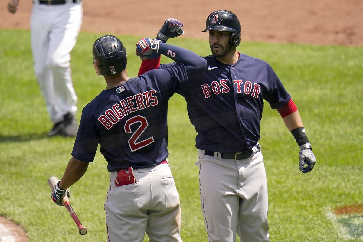 J.D. Martinez of the Red Sox is greeted by Xander Bogaerts after the first of his three solo home runs.