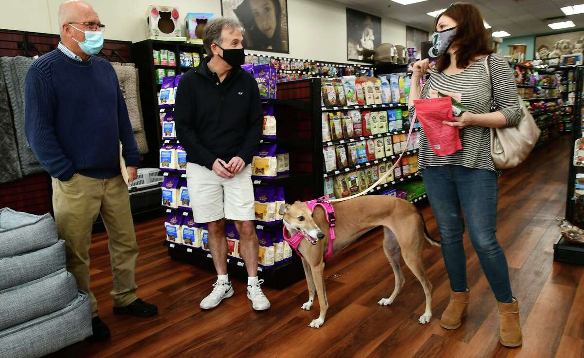 Choice Pet owner Rick Shanley, left, and CFO Steve Rossetter, greet customer Geraldine Matthews and her Greyhoud rescue, Lu Lu, at the store's grand opening event in Ridgefield on April 10.