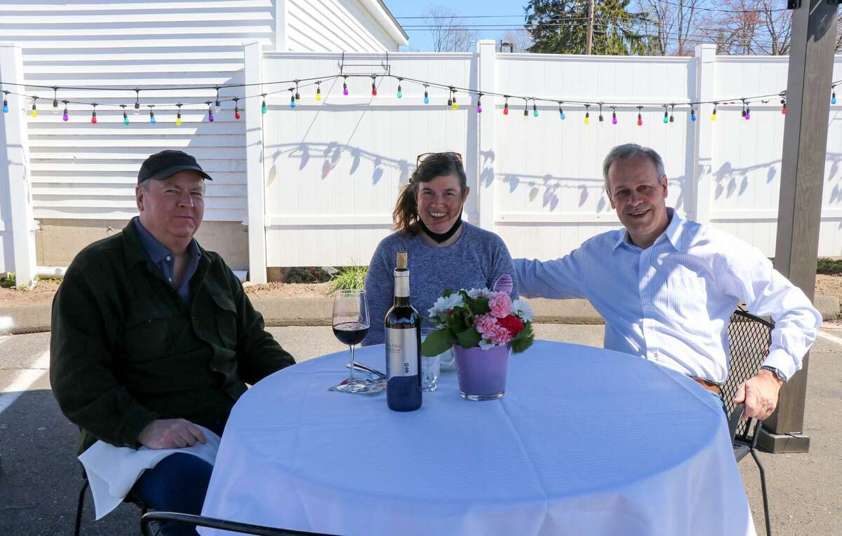 Ellen Mavuli, center, and her brother Steve Casey, right, join Len Hall at a temporary outdoor dining table at Gusto Trattoria in Milford.