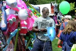 Maurice Clark sells inflatable animals and other novelties for children at Village Fair Days friday, July 28, 2017. This is the fair's 50th anniversary.