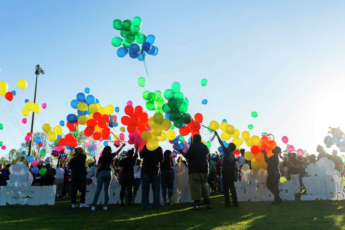Family and friends of Porsha Branch, who was killed by a drunk driver along with her three young children, Drake, King and Messiah, release balloons during a vigil for the family on Thursday evening, March 25, 2021, at Meyer Park in Spring.