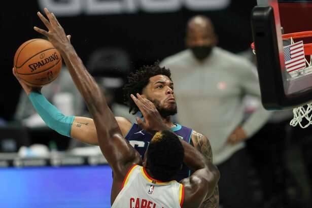 Charlotte Hornets forward Miles Bridges, left, prepares to dunk over Atlanta Hawks center Clint Capela, right, during the fourth quarter of an NBA basketball game in Charlotte, N.C., Sunday, April 11, 2021. (AP Photo/Nell Redmond)
