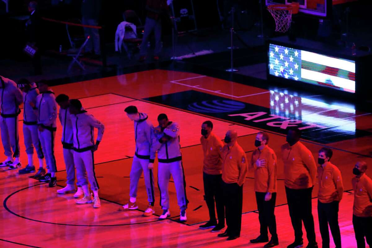 The Houston Rockets stand on the court for the National Anthem before the start of the first half of an NBA basketball game at Toyota Center, in Houston, Thursday, February 11, 2021.