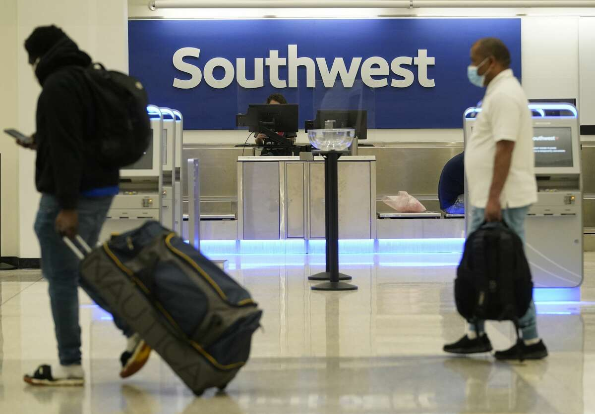 People in Terminal A at George Bush Intercontinental Airport pass by the Southwest Airlines counter Friday, April 9, 2021 in Houston.
