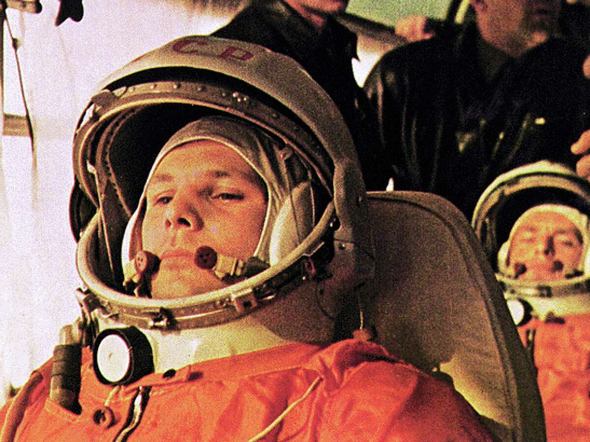 In this image Yuri Gagarin, the first man in space, is on the bus on the way to the launch. The cosmonaut behind Gagarin is German Titov, the back-up pilot.