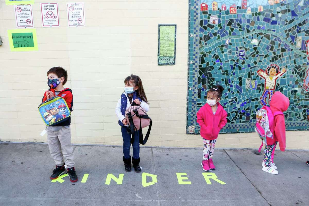 Pre-K students stand in line to check-in on the first day of in-person school in over a year at Bryant Elementary on April 12 in San Francisco. The district is looking for outside experts to help guide the process to fully reopen schools in August.