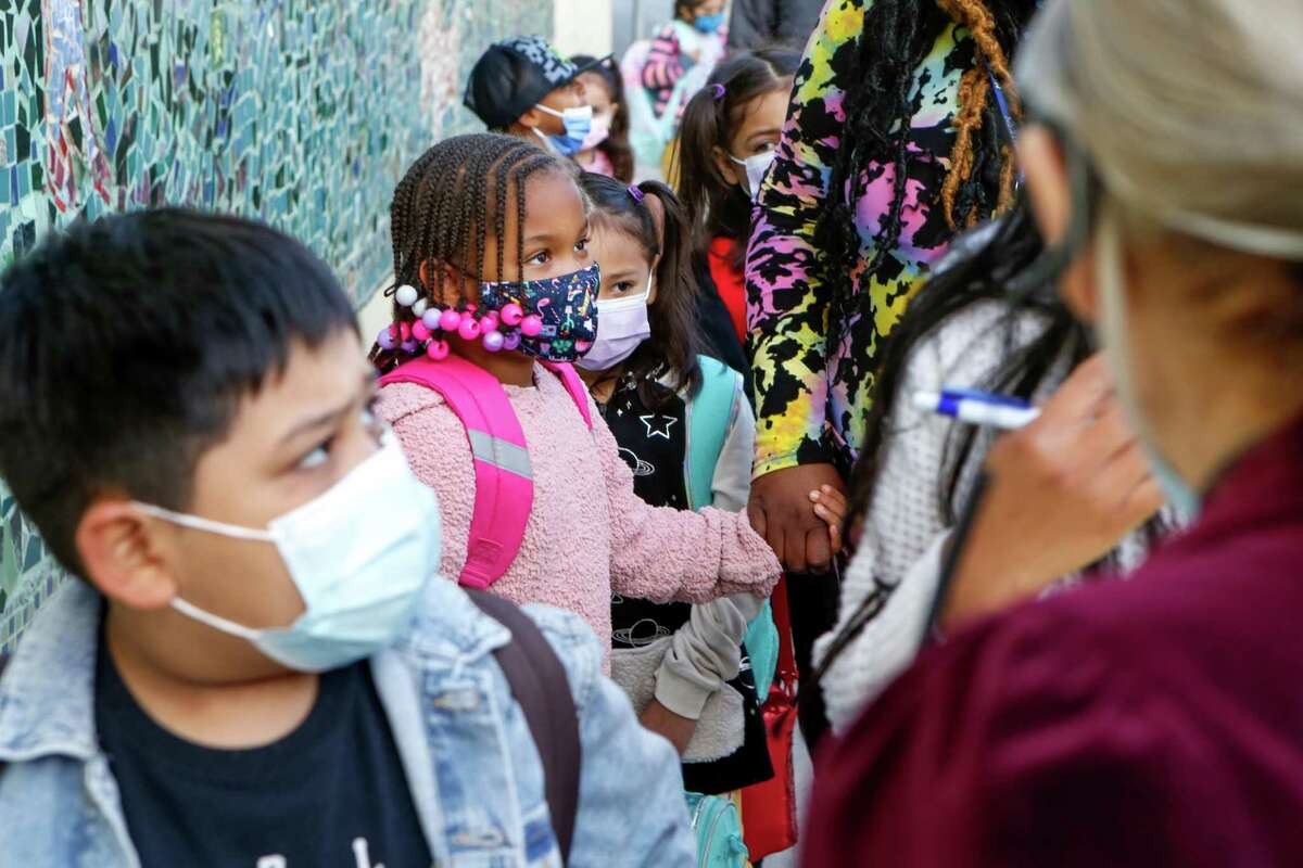 Children stand in line to check in at the first day of in-person classes in over a year at Bryant Elementary School on Monday, April 12, 2021 in San Francisco, Calif.