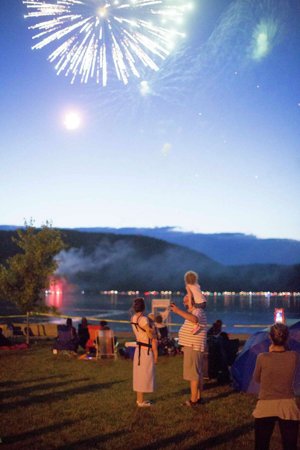 Fireworks explode behind Anton Belousov, who works in Danbury at Wells Fargo, his wife, Olga Volodiaeva, and children Eva and Mia Belousov at the Danbury Town Park where fireworks were launched at Candlewood Lake the night of Saturday, June 24.